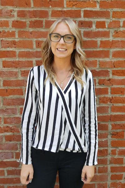 Samantha Nelson wearing a black and white striped blouse standing in front of a red brick wall.
