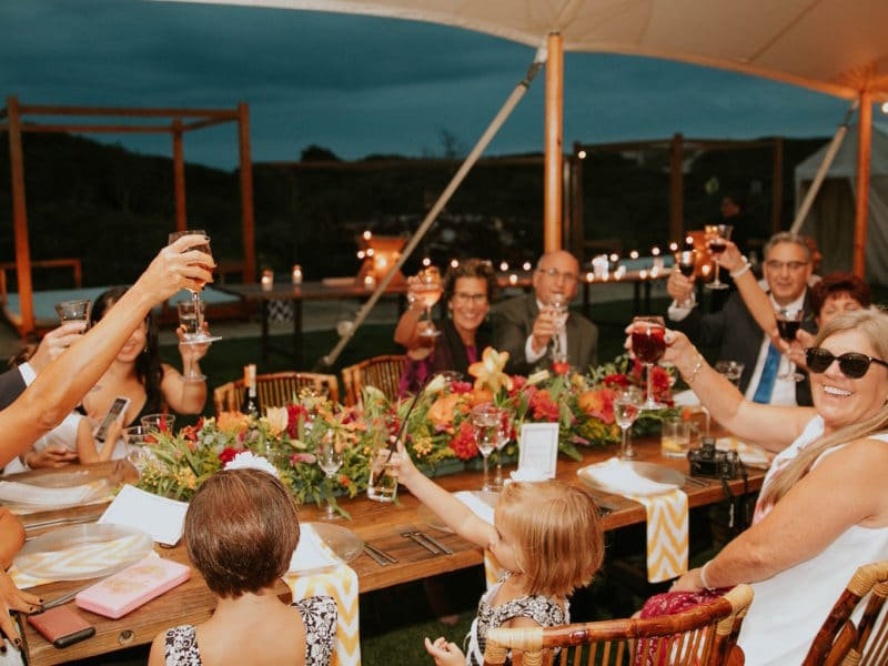 People seated around a table celebrating an event with a group cheers of their beverages