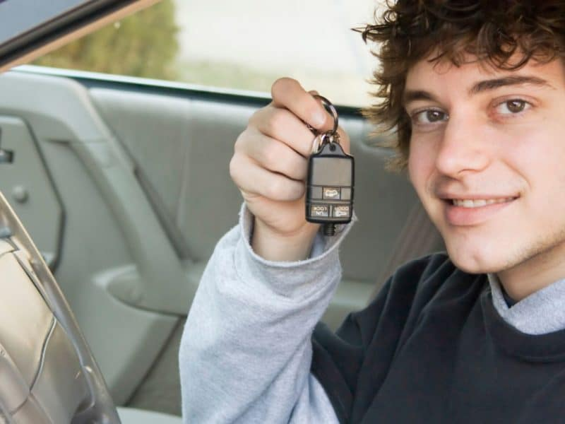 Teen driver sitting in the driver seat holding up car keys with an excited look on his face.