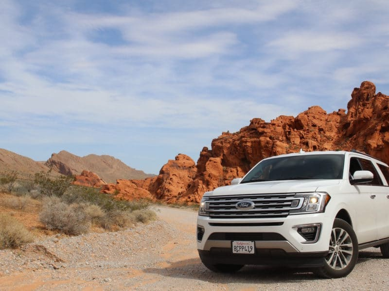 A white Ford SUV is parked at the bottom of a desert cliff.