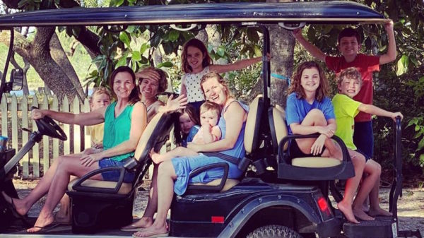 A family sits happily in an 8 person golf cart.